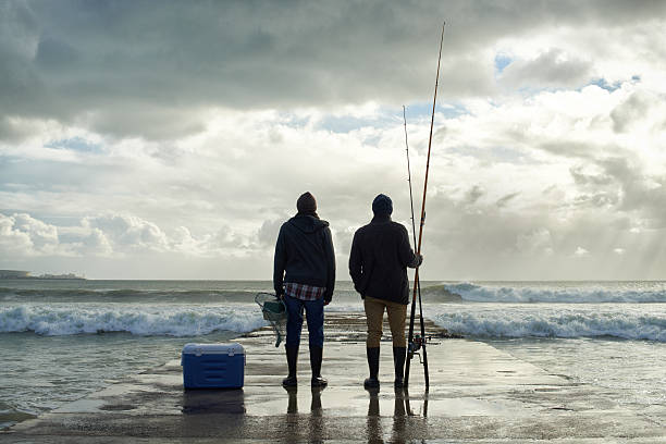The sea was generous today... Shot of two young men fishing at the ocean in the early morning fisherman stock pictures, royalty-free photos & images