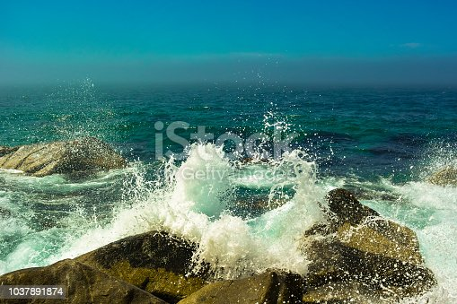 Seascape, stone cuts waves forming foam. Splashes of the sea, waves