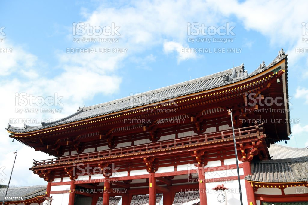 The second antique wooden archway entrance of Todaiji temple with green tree and blue sky background. stock photo