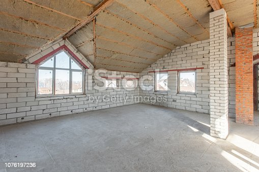 466705128istockphoto The second attic floor of the house. overhaul and reconstruction. Working process of warming inside part of roof. House or apartment is under construction, remodeling, renovation, restoration. 1076197236