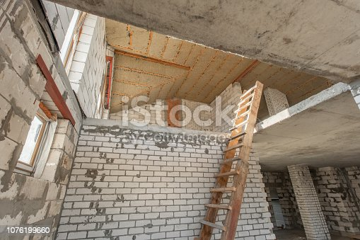 466705128istockphoto The second attic floor of the house. overhaul and reconstruction. Working process of warming inside part of roof. House or apartment is under construction, remodeling, renovation, restoration. 1076199660