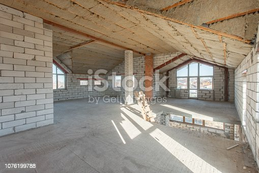 466705128istockphoto The second attic floor of the house. overhaul and reconstruction. Working process of warming inside part of roof. House or apartment is under construction, remodeling, renovation, restoration. 1076199788