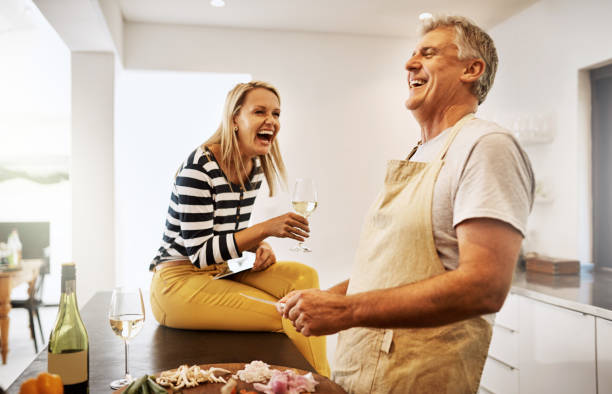 The secret is to never stop having fun Shot of a happy mature couple keeping each other company in the kitchen mature couple stock pictures, royalty-free photos & images