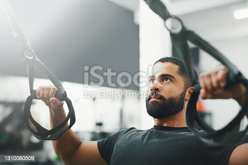 Shot of a man using suspension straps while working out in the gym