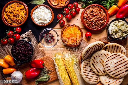 View from above of a wooden rustic table with several ingredients for cooking and filling arepas, typical Latin American food.  In the image we can see arepas, meat, chicken, black beans, cheeses, avocado, corn and some spices and vegetables