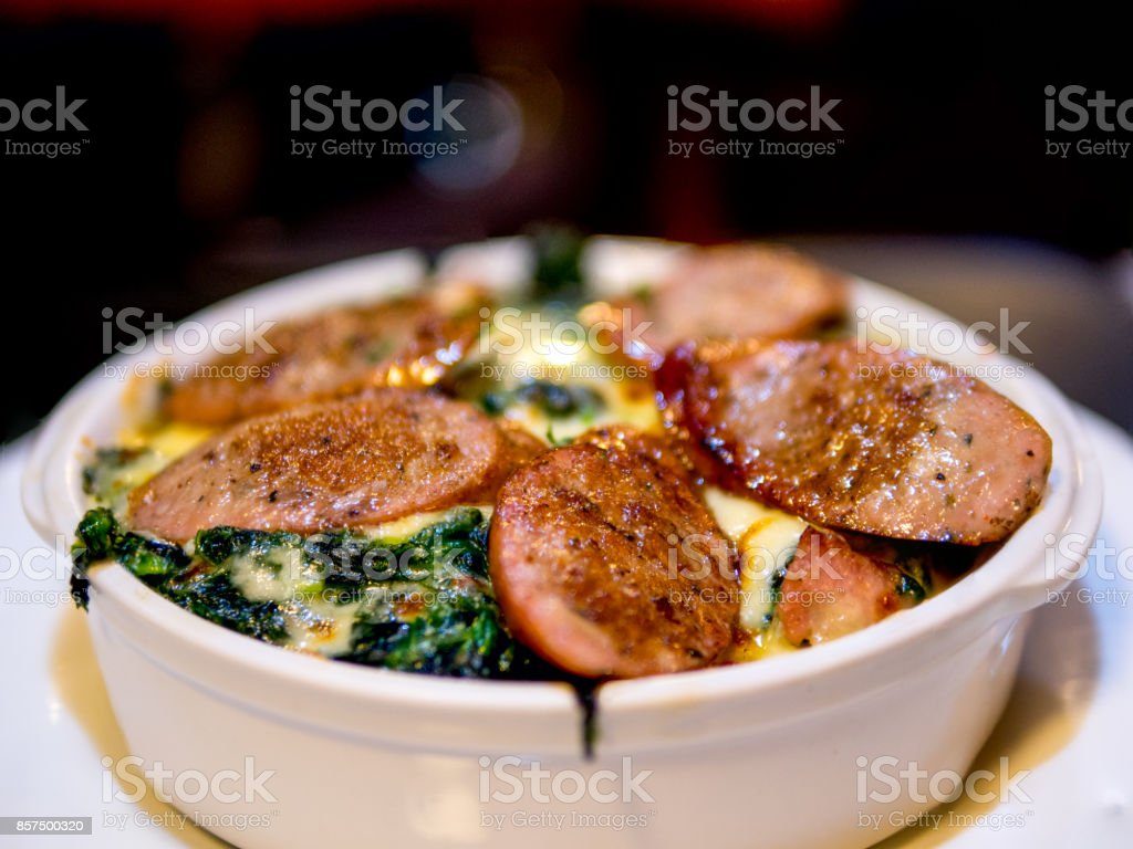 The selective focused and closeup image of braked spinach with cheese and sausage in a whit bowl. stock photo