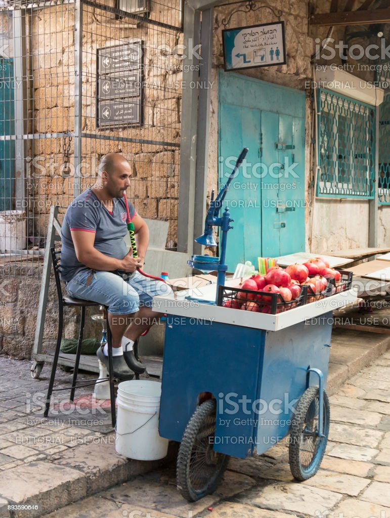 The seller of freshly squeezed juices sits and smokes nargila in anticipation of buyers on the market in the old city of Acre in Israel stock photo