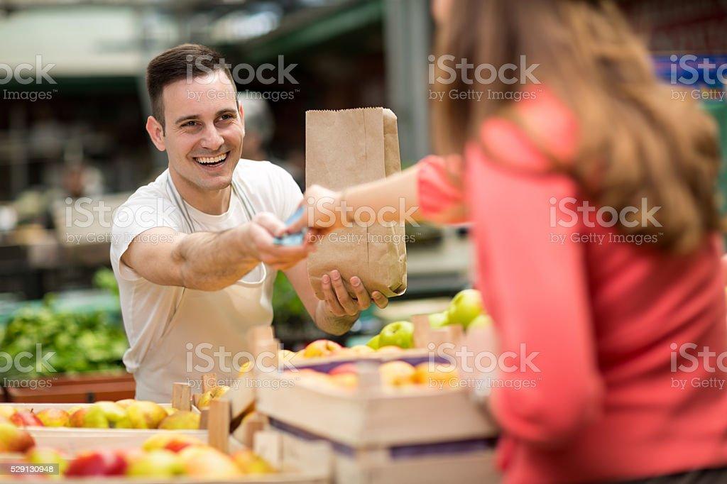 the seller takes money at farmer's market stall stock photo