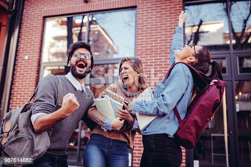 Three students laughing and rejoicing on the street