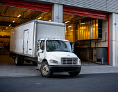 The middle-duty white day cab compact semi truck for local shipping and delivery services with long box trailer leaves the gate of multistory building after unloading the delivered cargo.