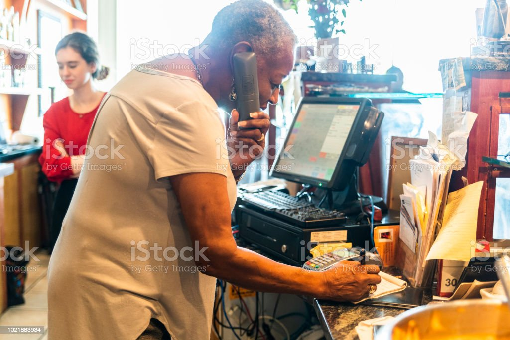 The senior, 77-years-old African-American woman receiving the phone order and reservation by phone in the small local restaurant – zdjęcie