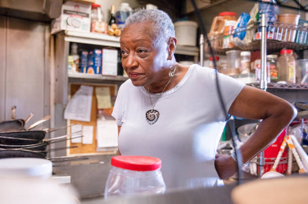 The senior active entrepreneur businesswoman, African-American, checking out the kitchen of her restaurant stock photo