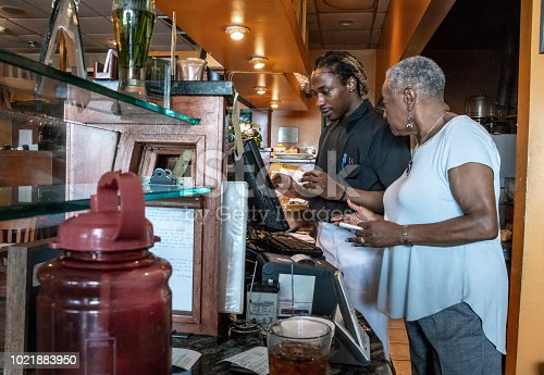 istock The senior African-American businesswoman working with her employee, the young Black man, with the cash register in the restaurant 1021883950