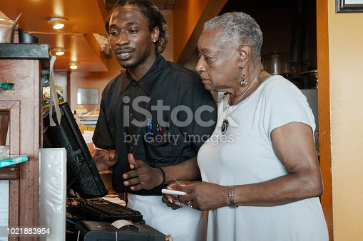 istock The senior African-American businesswoman working with her employee, the young Black man, with the cash register in the restaurant 1021883954