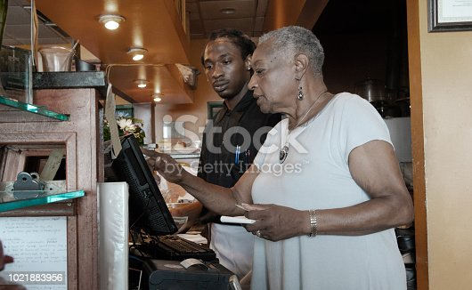istock The senior African-American businesswoman working with her employee, the young Black man, with the cash register in the restaurant 1021883956