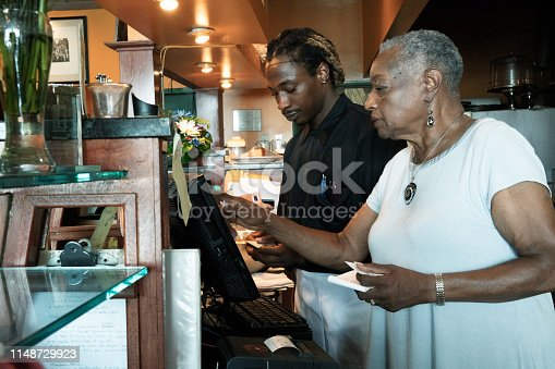 istock The senior African-American businesswoman working with her employee, the young Black man, with the cash register in the restaurant 1148729923