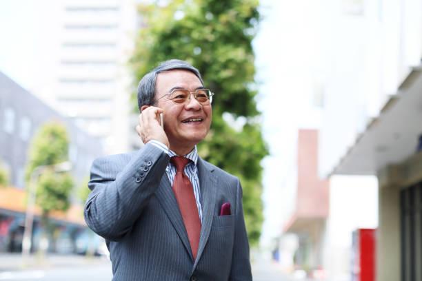 the senior businessman who talks on the telephone - pensionati lavoratori foto e immagini stock