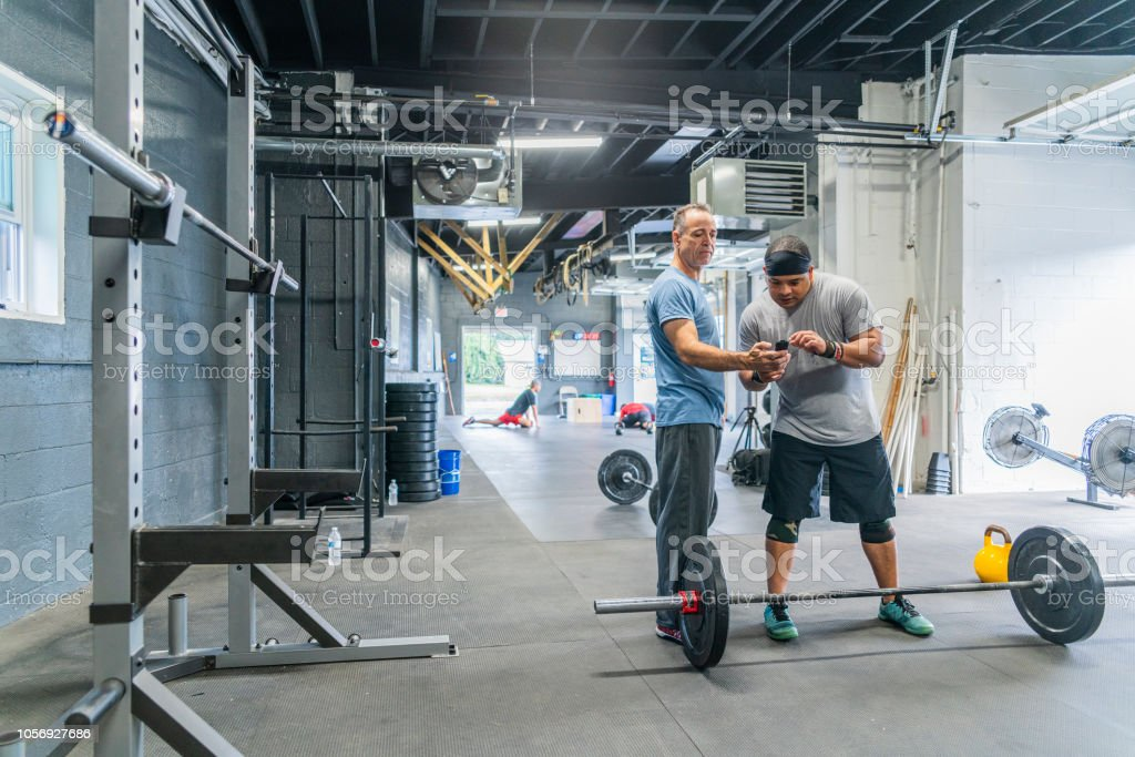 The senior Latino man, the coach, showing the fitness results to the...