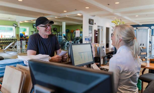 Der ältere Mann bittet um Informationen über die Turnhalle und ein Gespräch mit der leitenden silberhaarigen Frau, die an der Rezeption arbeitet. – Foto
