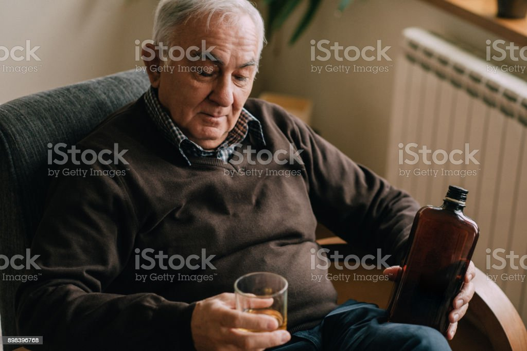 The senior man drinking whiskey in the living room stock photo