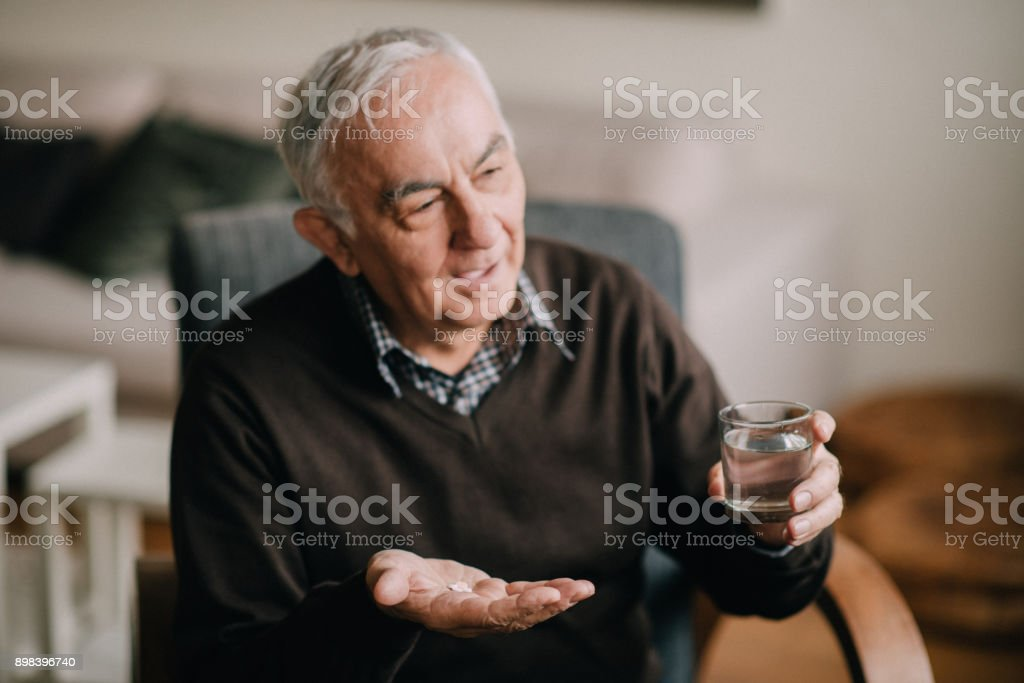 The senior man holding pills in one hand and water in the other one stock photo