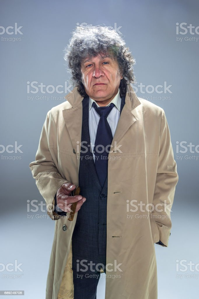 The senior man with cigar as detective or boss of mafia on gray studio background stock photo