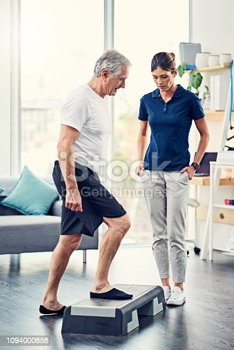 Full length shot of an attractive young female physiotherapist working with a senior male patient