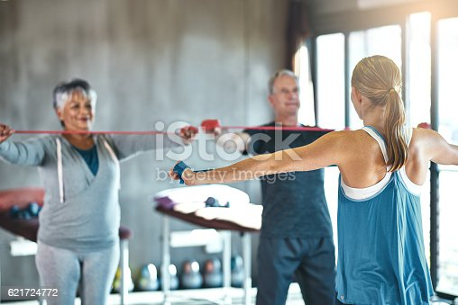 Shot of a senior man and woman using resistance bands with the help of a physical therapist