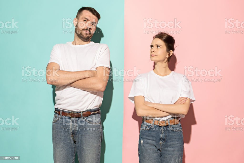 Serious man and woman looking at camera on trendy pink and blue...