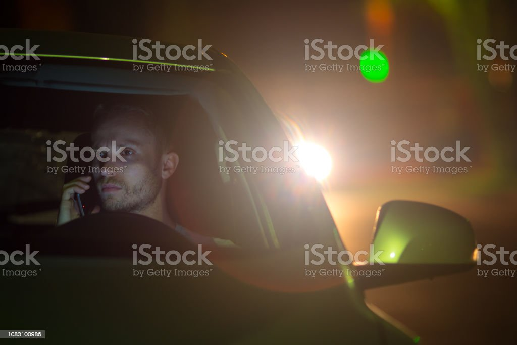 The serious man sit inside the car and phone. Evening night time