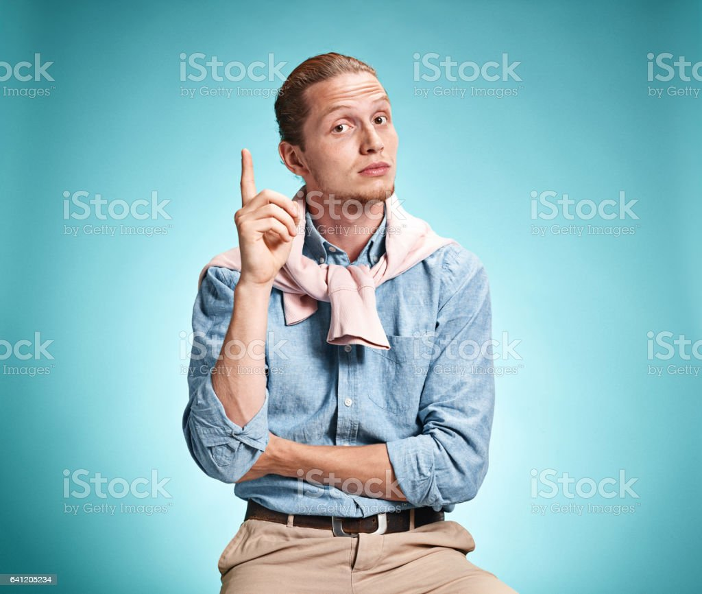 The serious young man over blue background stock photo