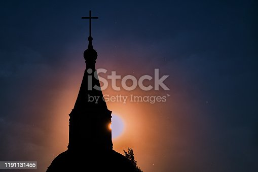 The setting sun shines on the dark blue sky from behind the christian cathedral. Silhouette of the catholic church at sunset.