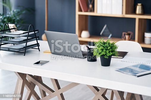 Shot of a laptop and other various items on a work desk in a modern office