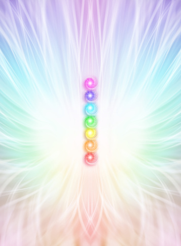 column of  seven chakras on a beautiful outward radiating rainbow coloured energy formation background with copy space