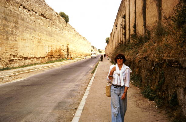 The seventies. A woman is walking between the city wall of Meknes, Morocco. stock photo