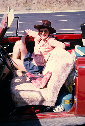 istock The Seventies. A young woman enroute on the streets of Turkey with a red beetle convertible for vacation. 910643608