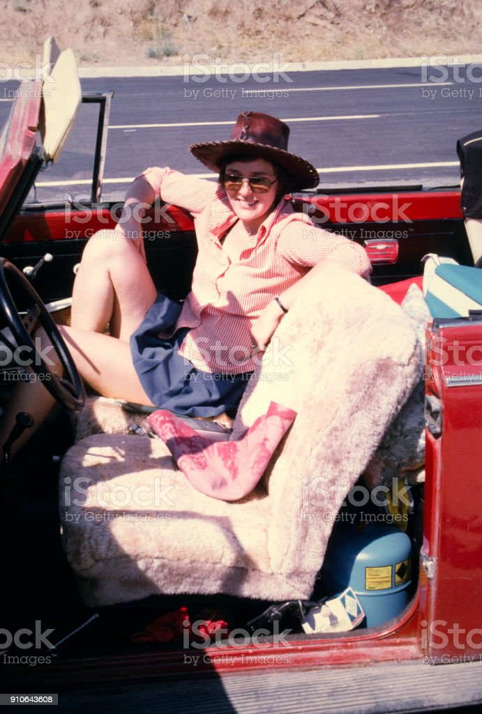 The Seventies. A young woman enroute on the streets of Turkey with a red beetle convertible for vacation. stock photo