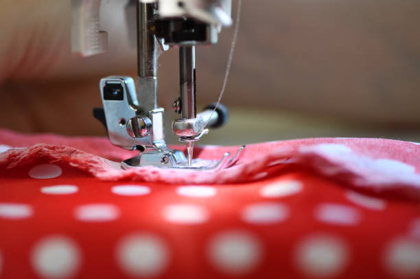 the sewing machine and item of clothing - embroidery machine stock pictures, royalty-free photos & images