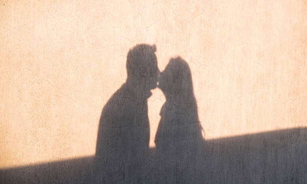 The shadow on the wall of loving couple kissing - foto de acervo