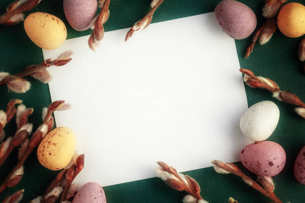 The sheet of paper on darkly green background with Easter eggs and branches of a willow, an easter background and mock up stock photo