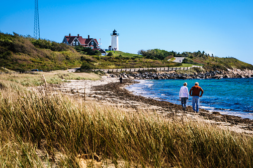 Woods Hole, Massachusetts, USA - October 11, 2010: A young couple walk along the beach below Nobsca Lighthouse in Woods Hole searching for sea shells that may have washed ashore.