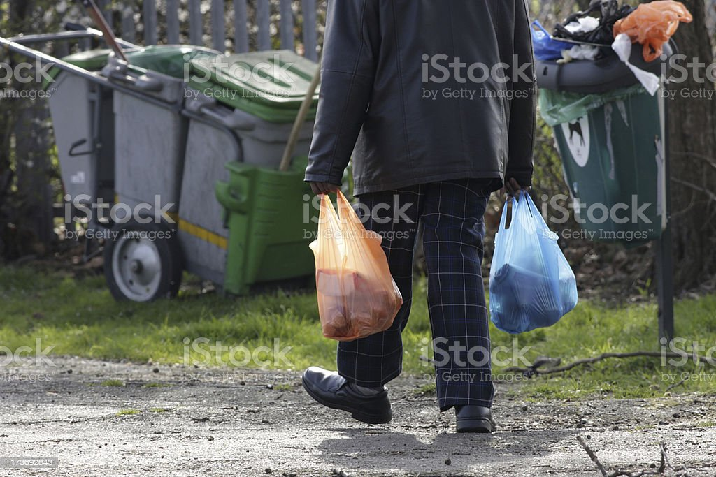 Man plodding home carrying heavy shopping in plastic bags stock photo