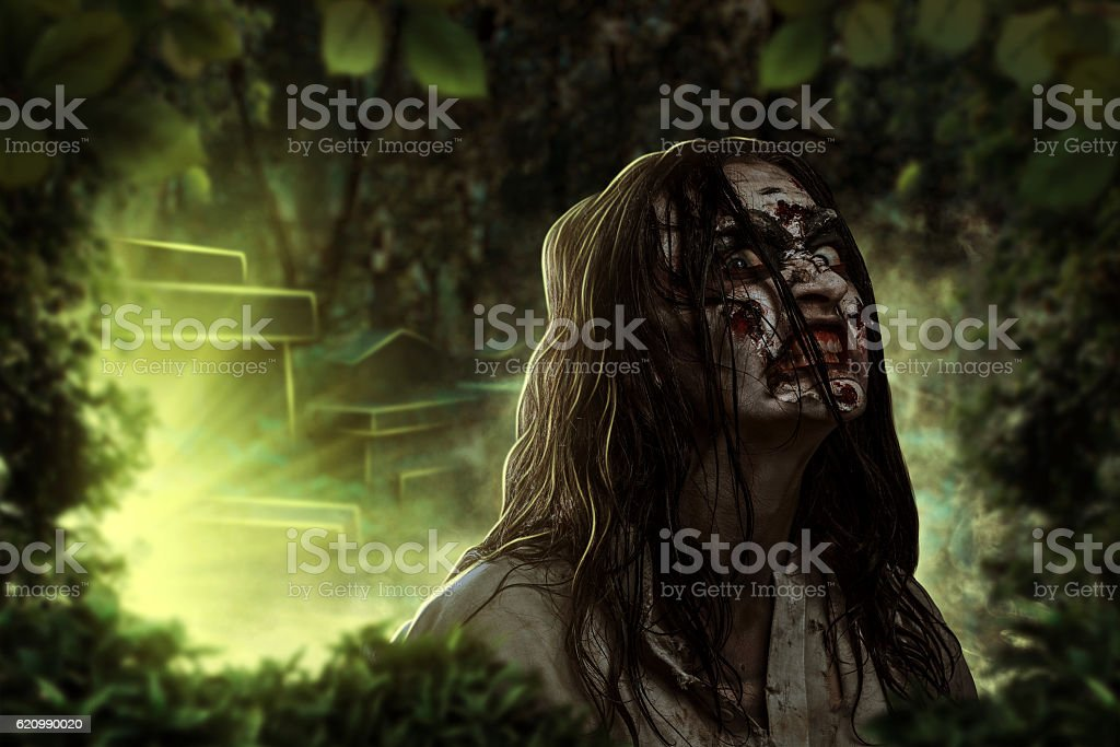 The shouting female zombie. Cemetery. Halloween. foto royalty-free