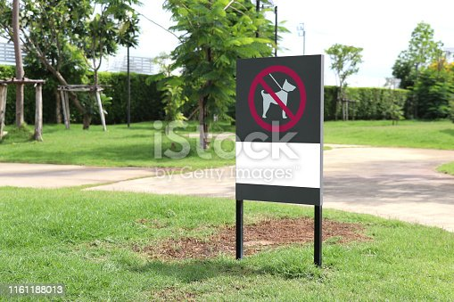 The sign indicates that dogs are not allowed in this area. Signs forbidding dogs from entering the park.