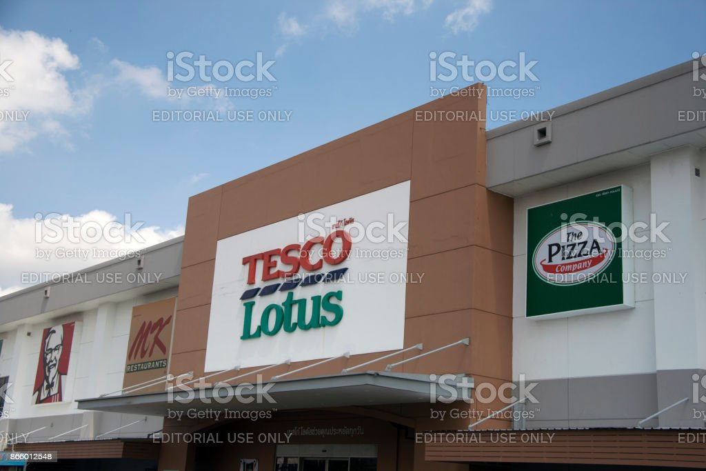 The sign name of Tesco Lotus Discount Store on the board with Other Stores and blue sky background.
