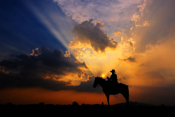 The silhouette of a cowboy on horseback at sunset on a  background The silhouette of a cowboy on horseback at sunset on a  background ranch stock pictures, royalty-free photos & images