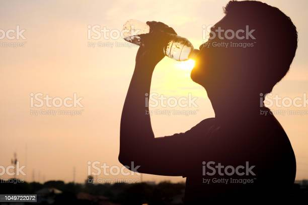 Photo of The silhouette of a man drinking a refreshing bottle of water on a sunset background