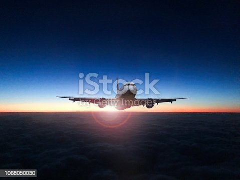 816320512 istock photo The silhouette of a passenger plane flying in sunset. 1068050030