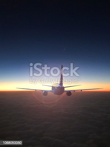 816320512 istock photo The silhouette of a passenger plane flying in sunset. 1068050050