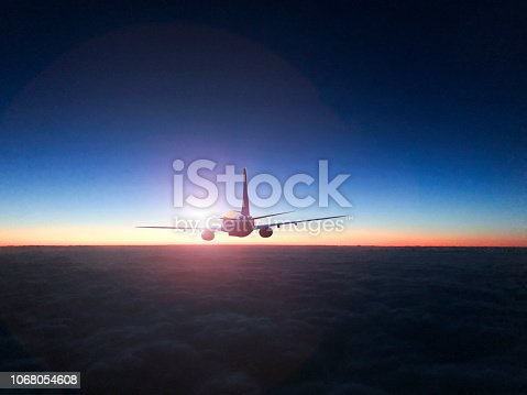 816320512 istock photo The silhouette of a passenger plane flying in sunset. 1068054608